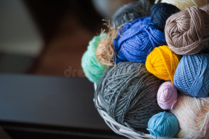 Colorful yarn balls in wicker basket on white stock photo
