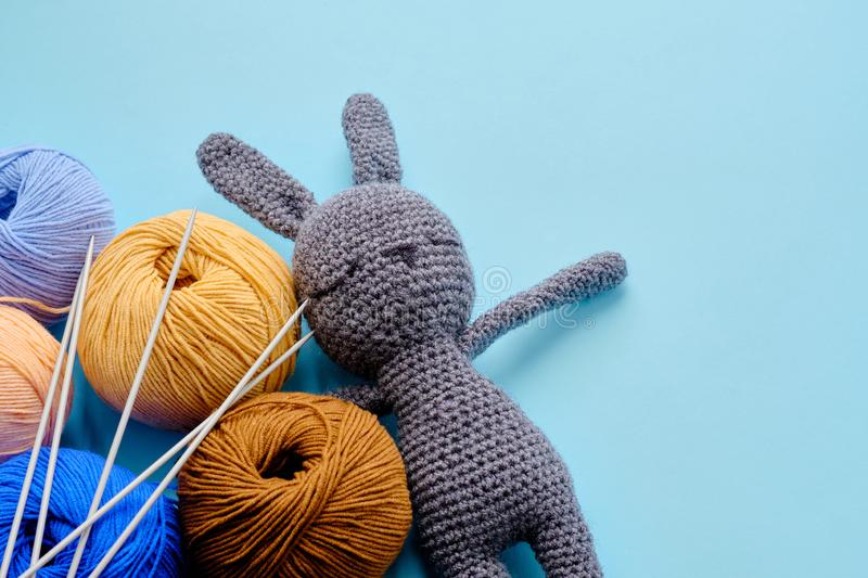 Colorful yarn clews with gray stuffed bunny and needles on the blue background. Concept of amigurumi toy making, handcrafting, stock photos