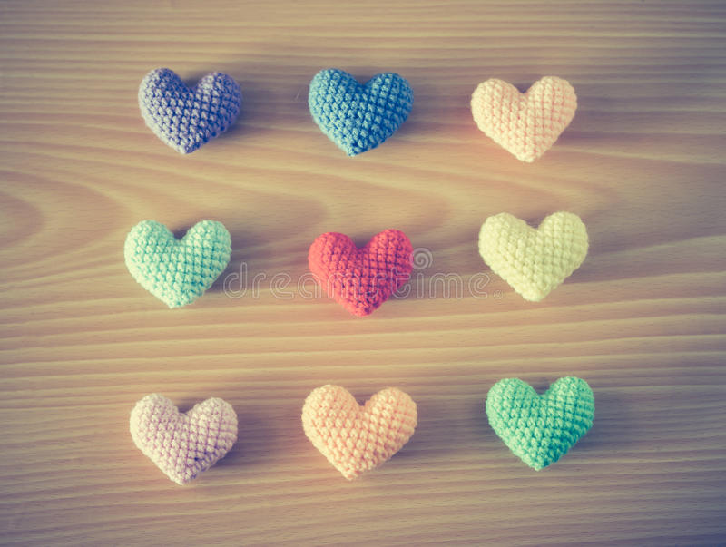 Colorful Yarn hearts on wood background. Colorful Yarn hearts on wooden background - vintage effect style stock photos