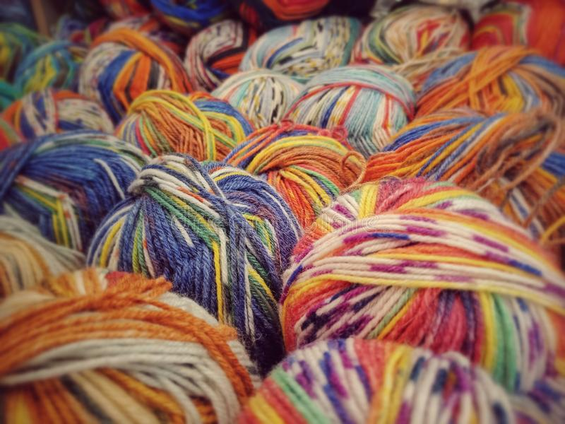 Colorful yarn on sell in shop. Blue, orange and various multicolored wool yarn on sale abstract art background ball bright clew closeup colorful coloured cotton stock images