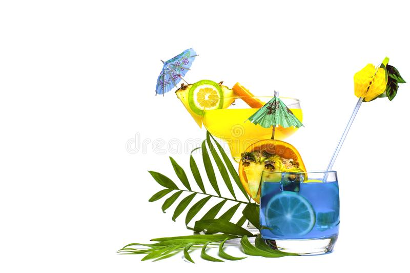 Colorful yellow and blue summer cocktails decorated with tropical fruits, umbrellas and straws on white background with palm tree stock photo