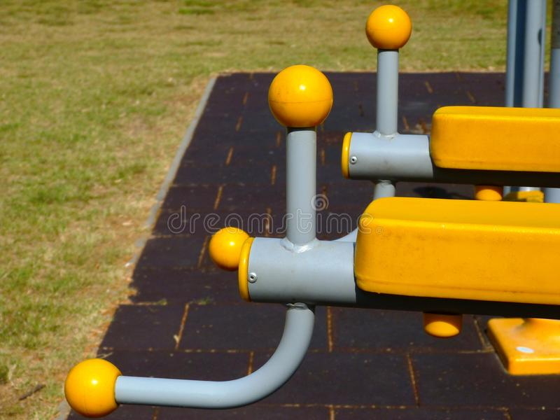 Yellow plastic exercise equipment detail in park. plastic grip on grey bent steel pipe frame. stock photos