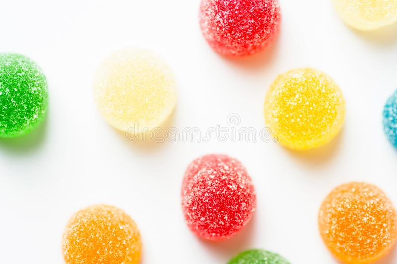 Colorful yellow red orange green gummy jelly candies coated with sugar arranged in pattern on white background. Kids birthday royalty free stock photo
