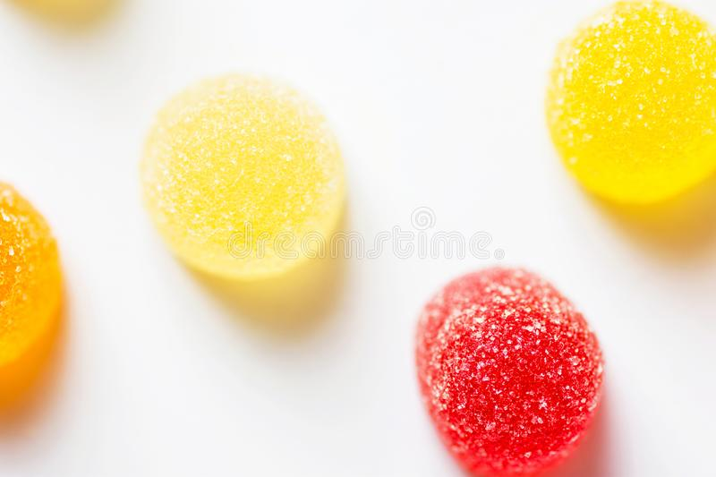 Colorful yellow red orange gummy jelly candies coated with sugar arranged in pattern on white background. Kids birthday party. Sweets fun concept. Creative royalty free stock photography