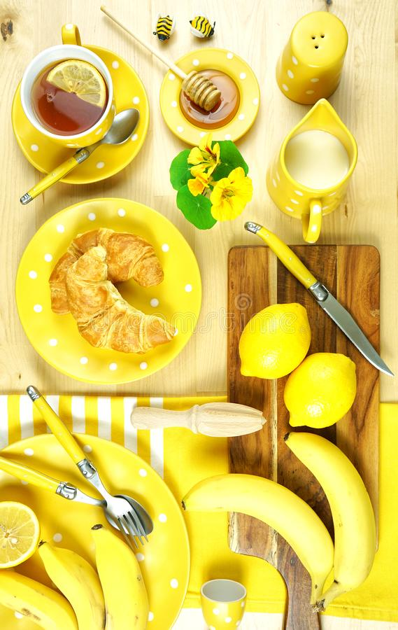 Colorful yellow theme breakfast brunch table setting flatlay. Modern bright colorful yellow theme morning breakfast or brunch table setting, flat lay royalty free stock photo
