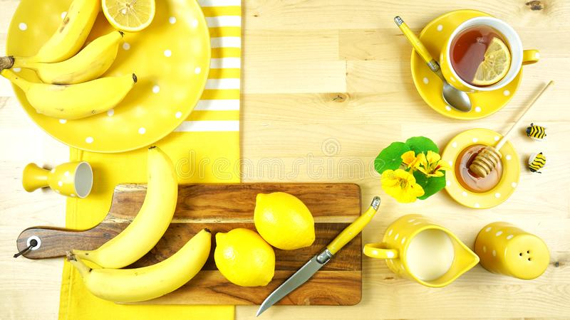 Colorful yellow theme breakfast brunch table setting flatlay. Modern bright colorful yellow theme morning breakfast or brunch table setting, flat lay with copy royalty free stock image