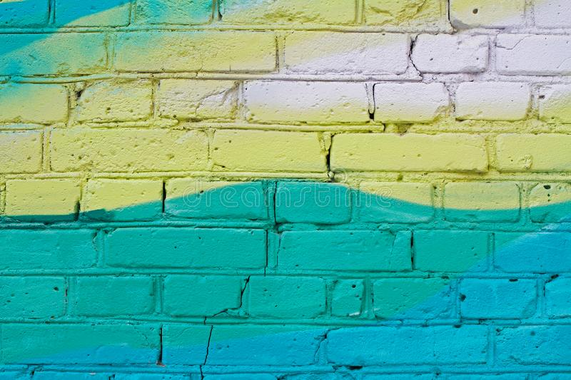 Colorful yellow and turquoise painted brick wall stock photo