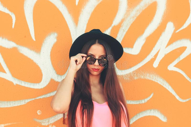 A colorful young girl looking at camera wearing a black hat and fashionable sunglasses stock photo