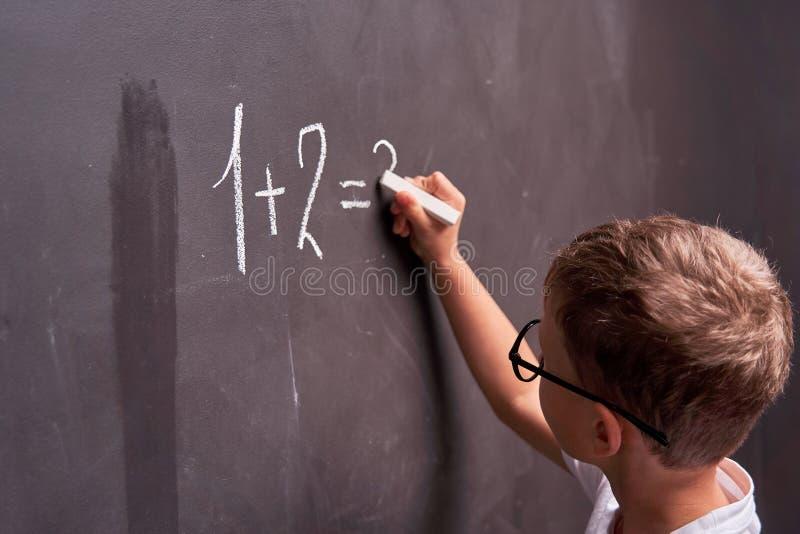 Colorfull B?cher, Zahlen und Zeichen Hintere Ansicht eines Schülers löst ein mathematisches Beispiel auf einer Tafel in einer Mat lizenzfreie stockfotos