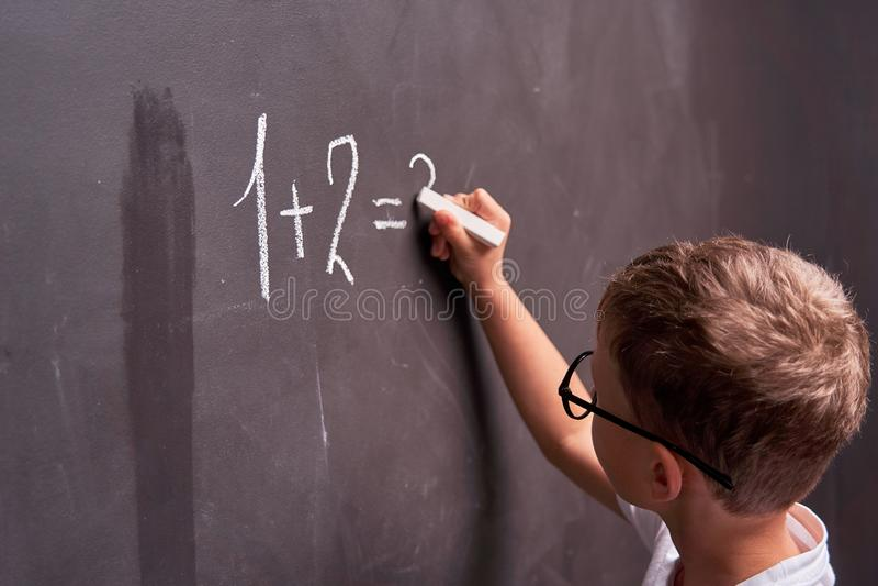 Colorfull b?cker, nummer och bokst?ver Den bakre sikten av en skolpojke löser ett matematiskt exempel på en svart tavla i en mate royaltyfria foton