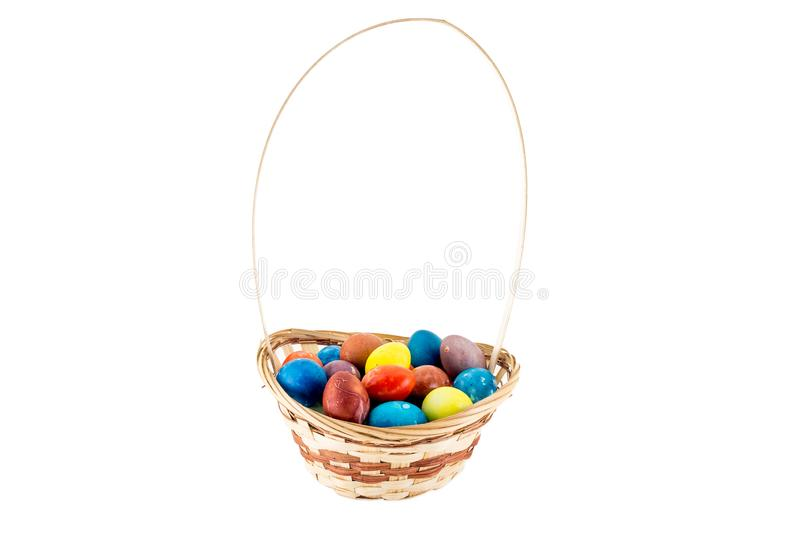 Colorfull Easter eggs in wicker basket isolated on white background royalty free stock image