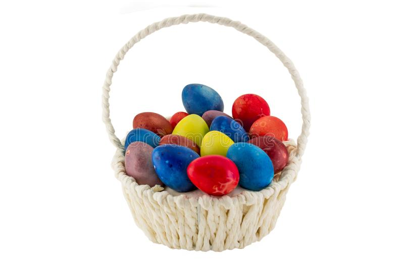 Colorfull Easter eggs in wicker basket isolated on white background royalty free stock photography
