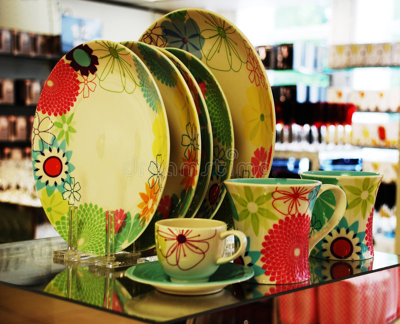 Colorfull plates. And tea cups on glass royalty free stock image
