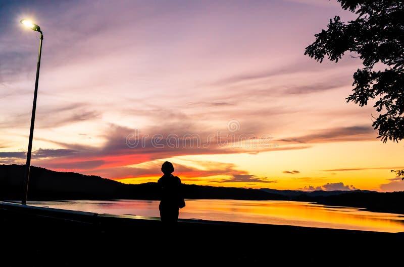 Colorfull-Sonnenunterganghimmel am See der Verdammung mit Schattenbild der Frau auf der Verdammungskante stockbilder