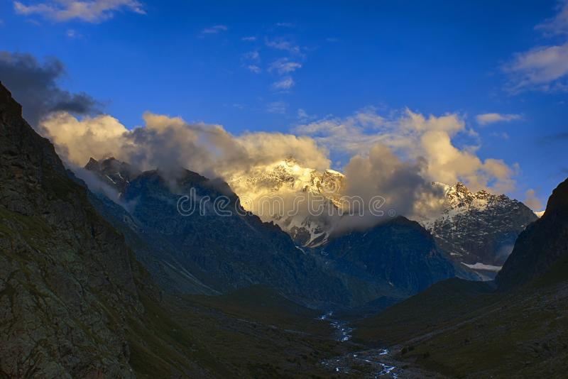 Colorfull sunset sky, clouds and mountains in high valley. With river. Huge icy peaks stock image