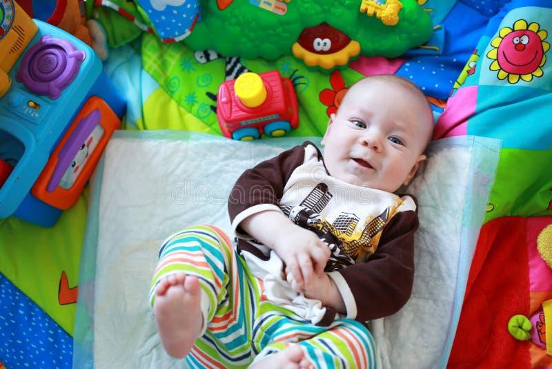 Colorfully ubierająca chłopiec bawić się na podłoga zdjęcie stock