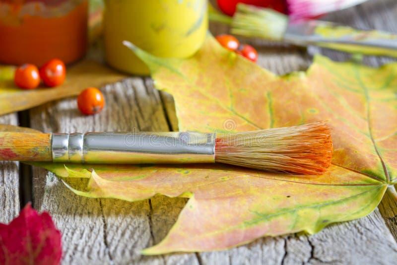 Colori dell'estratto di autunno con il pennello e le foglie fotografia stock libera da diritti