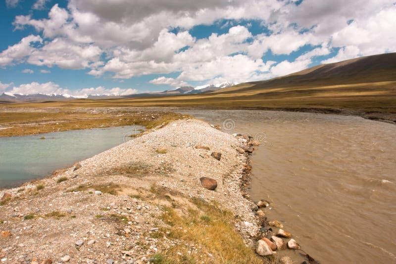 Colori differenti gli scorrimenti dell'acqua al piede della catena montuosa immagini stock libere da diritti