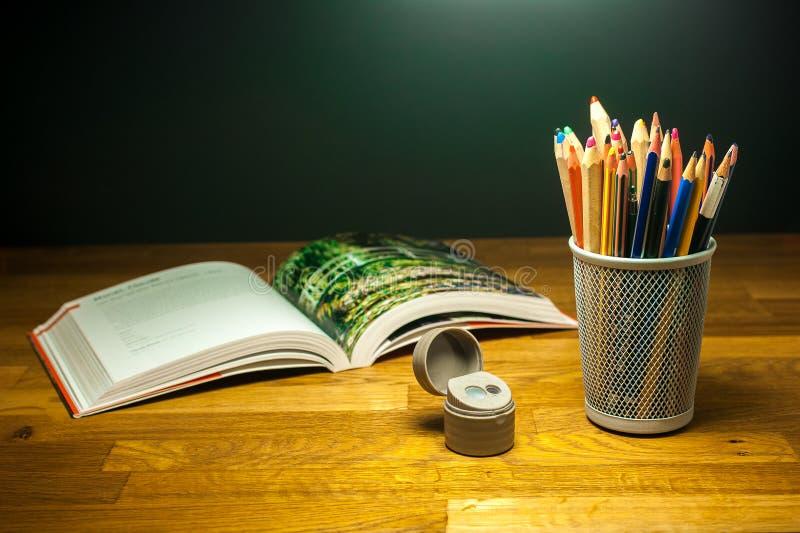 Colori i pastelli sulla tavola di legno accanto al temperamatite ed al libro illustrato per gli studenti di arte fotografie stock
