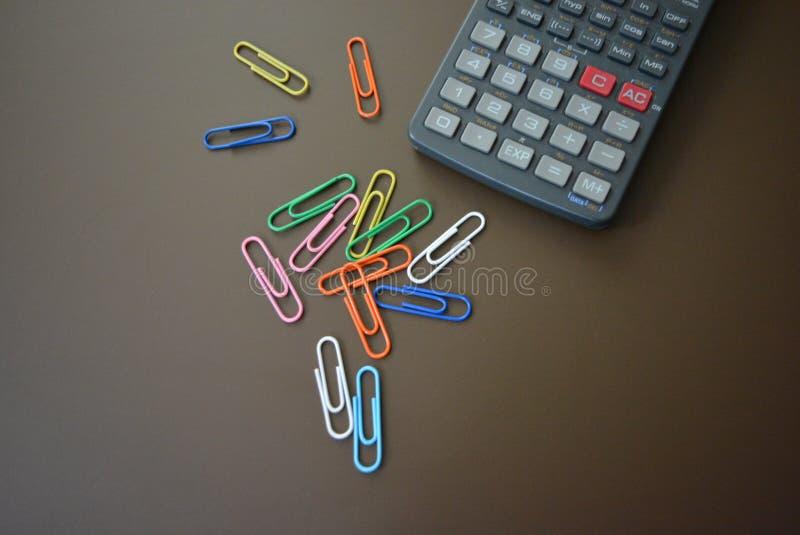 Colori le clip dei colori differenti con un calcolatore grigio su un fondo opaco marrone immagine stock libera da diritti