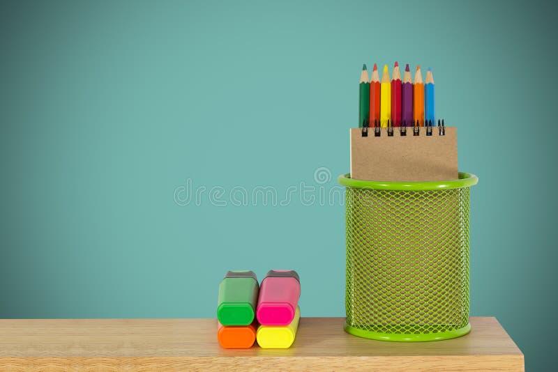 Colori le matite in un canestro verde del supporto con le penne di indicatore immagini stock libere da diritti
