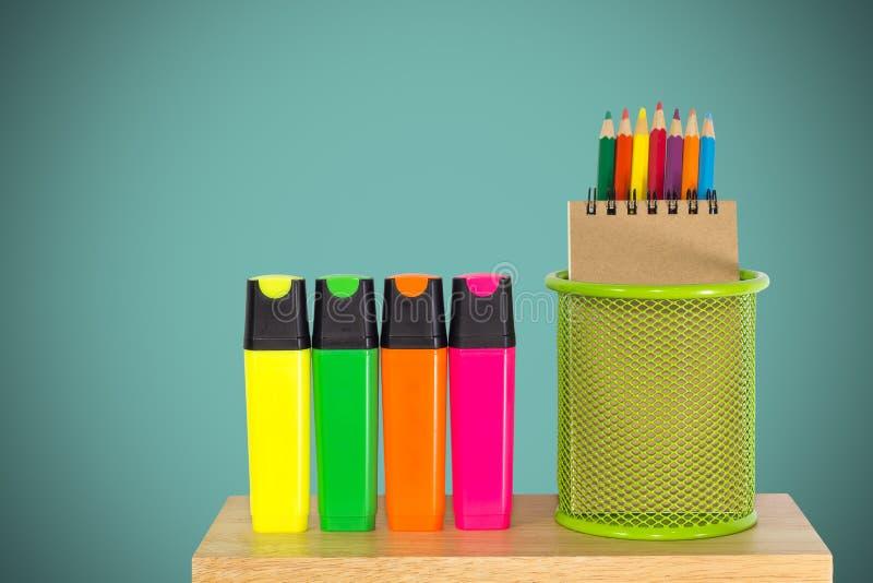 Colori le matite in un canestro verde del supporto con le penne di indicatore immagini stock