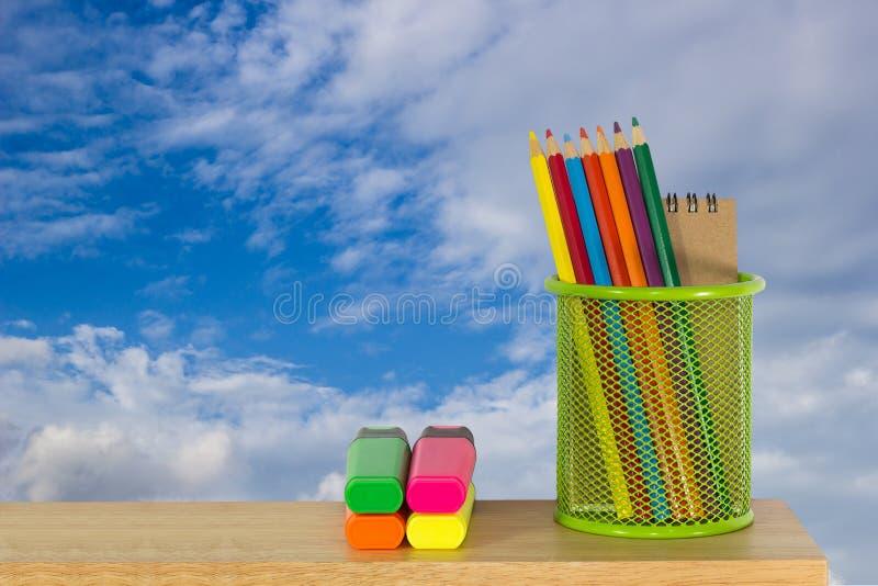 Colori le matite in un canestro verde del supporto con le penne di indicatore immagine stock libera da diritti