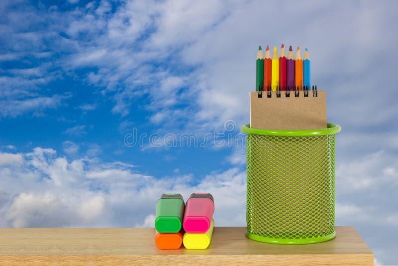 Colori le matite in un canestro verde del supporto con le penne di indicatore fotografia stock libera da diritti