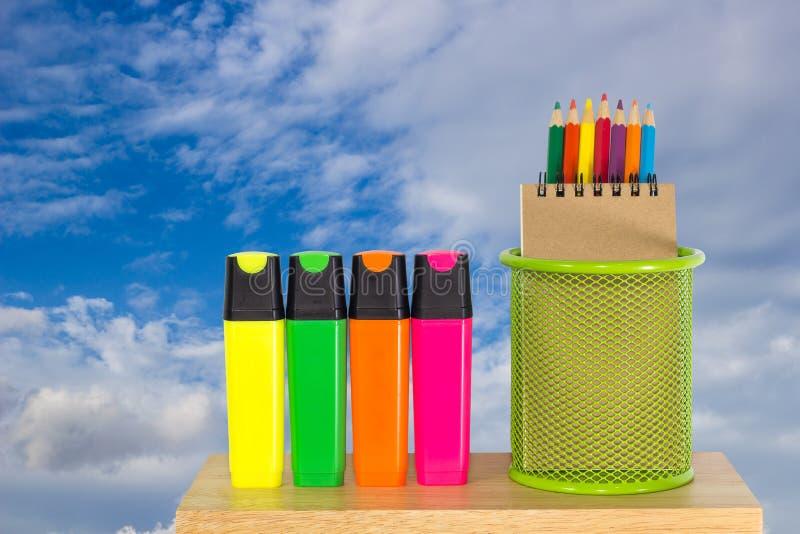Colori le matite in un canestro verde del supporto con le penne di indicatore fotografie stock