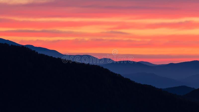 Colori luminosi di alba nautica sopra le montagne di Ridge blu immagini stock