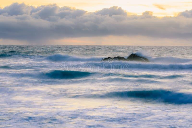 Colori pastelli del tramonto e dell'acqua serica da esposizione lunga delle onde che si schiantano dal faro del punto del piccion fotografie stock