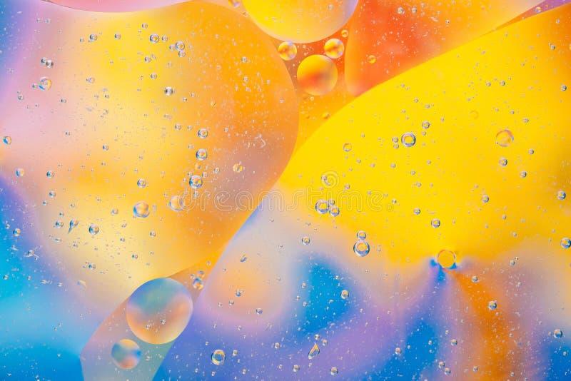 Colori rosa-rosso gialli della macro del fondo della bolla dell'olio dell'acqua di flusso acqua blu astratta del liquido fotografia stock