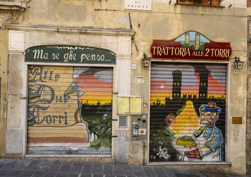 Coloridas puertas protectoras en los restaurantes de una calle de Génova, Italia imagen de archivo libre de regalías