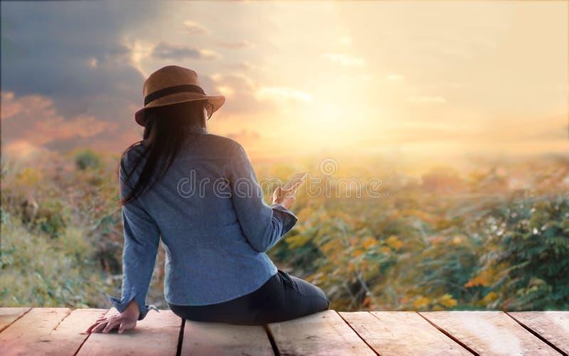Colorido abstracto, mujer que se relaja con smartphone a disposición encendido al aire libre en naturaleza rural de la puesta del fotos de archivo