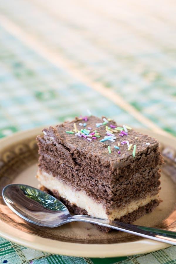 Colorido asperja en la torta de chocolate servida en la placa con la cuchara fotografía de archivo