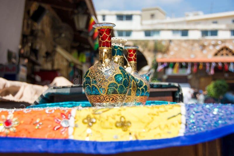 Colorido, botellas de Phoenecian del vintage en una tabla en un mercado del souk en el Oriente Medio imágenes de archivo libres de regalías
