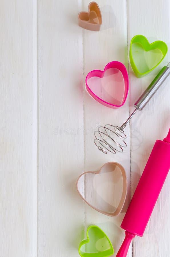 Colorido cueza las herramientas para la galleta en el fondo de madera blanco, visión superior fotos de archivo