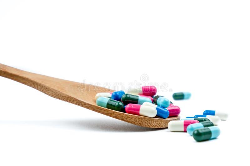 Colorido de comprimidos da cápsula dos antibióticos na colher de madeira estão derramando no fundo branco com espaço da cópia Uso foto de stock