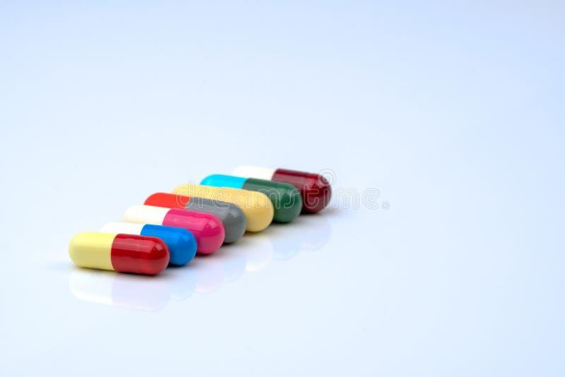 Colorido del antibiótico encapsula píldoras en fila en el fondo blanco con el espacio de la copia foto de archivo
