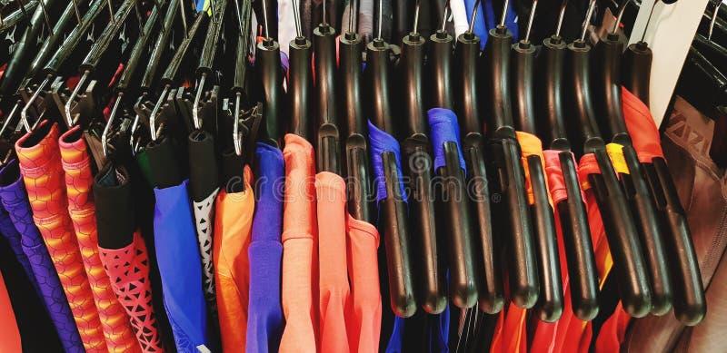 Colorido do sportswear do ` s das mulheres, as calças, as camisas e o waistcoat ou o cair da camiseta interioa no gancho plástico fotos de stock royalty free