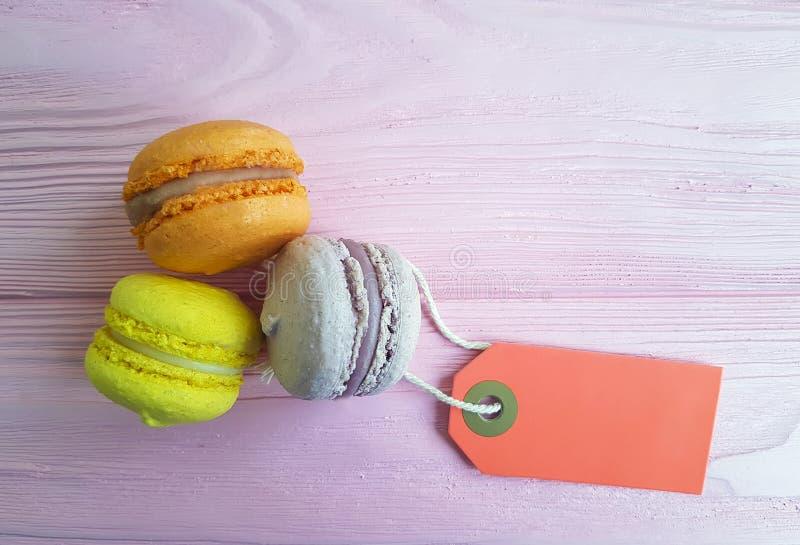 Colorido doce de Macaron em uma sobremesa de madeira cor-de-rosa da etiqueta do fundo fotos de stock royalty free
