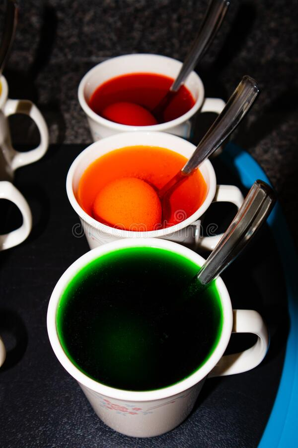 Coloring hard boiled Easter eggs in coffee cups stock photo