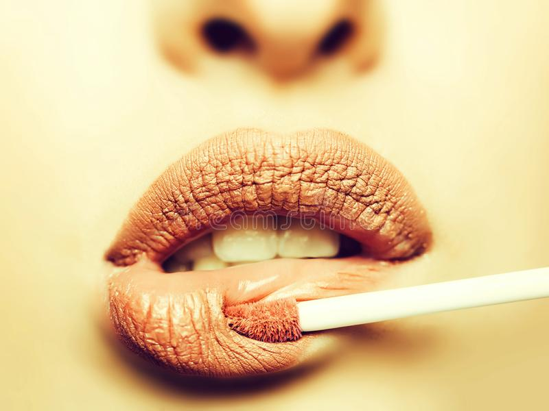 Coloring lips with gloss stick. Coloring lips of pretty girl with gloss stick applicator beige pink color makeup stock image
