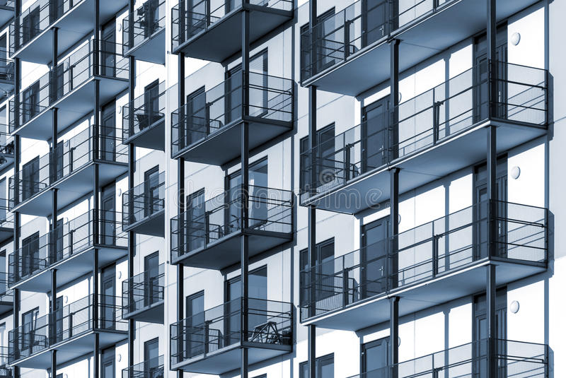 Colorized residential building background. Blue colorized construction background picture of modern apartment building with balconies stock photo