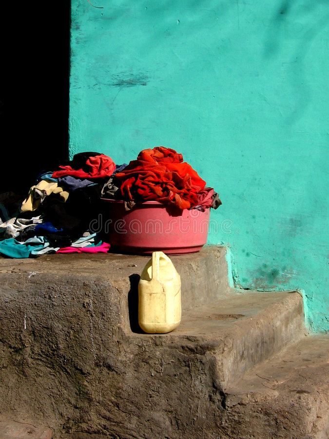 Colors. Bucketful of clothes in front of a bright colored wall in a traditional but poor Indian house royalty free stock photography