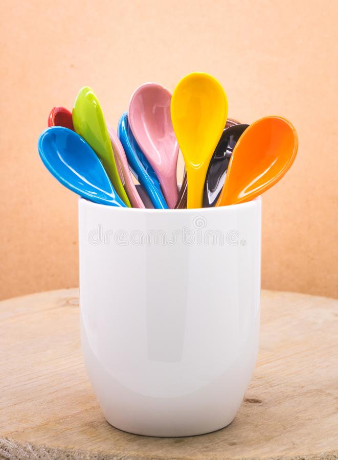 Colors ceramics spoon in mug on wooden backdrops. Colorful concept stock photography