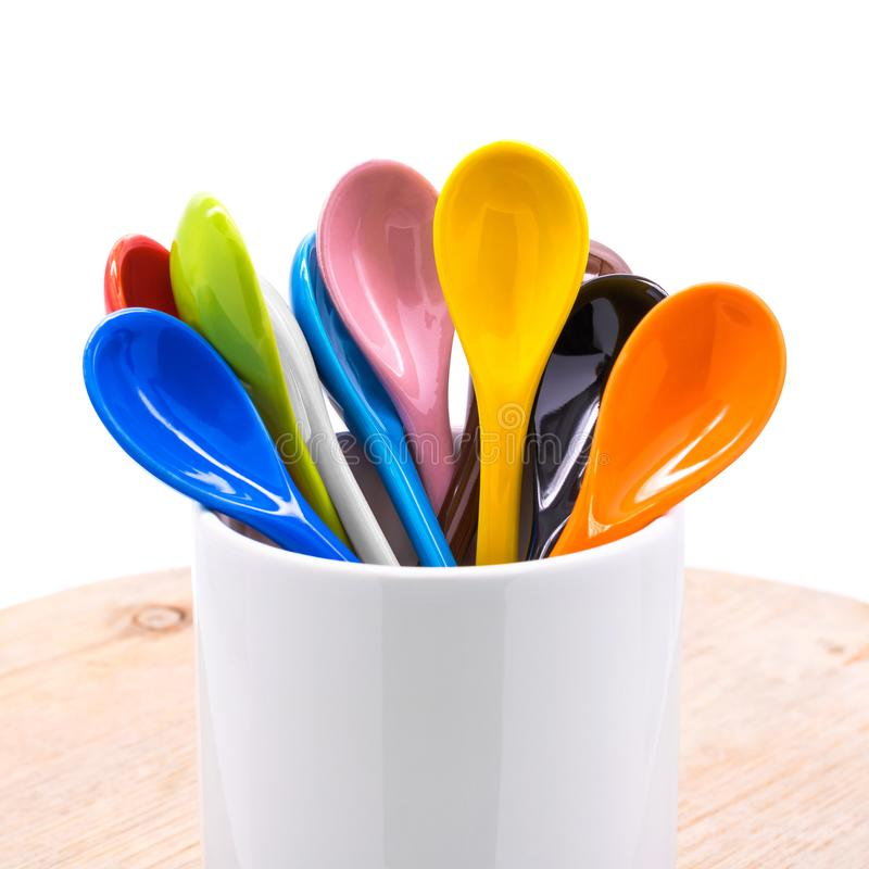 Colors ceramics spoon in mug on wooden backdrops. Colorful concept royalty free stock images