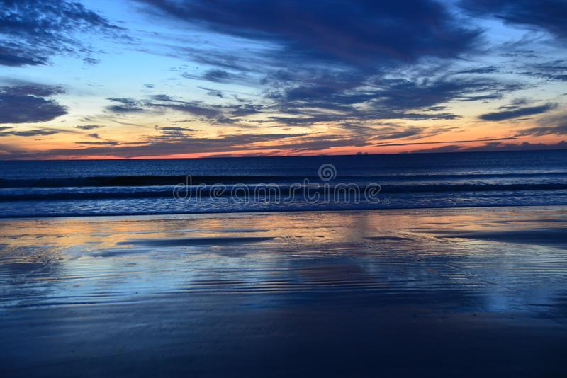 Colors change as the sun sets in the west and darkness falls over the ocean. The waves bring water to the beach tidal pools and abeautiful reflection of color stock photo