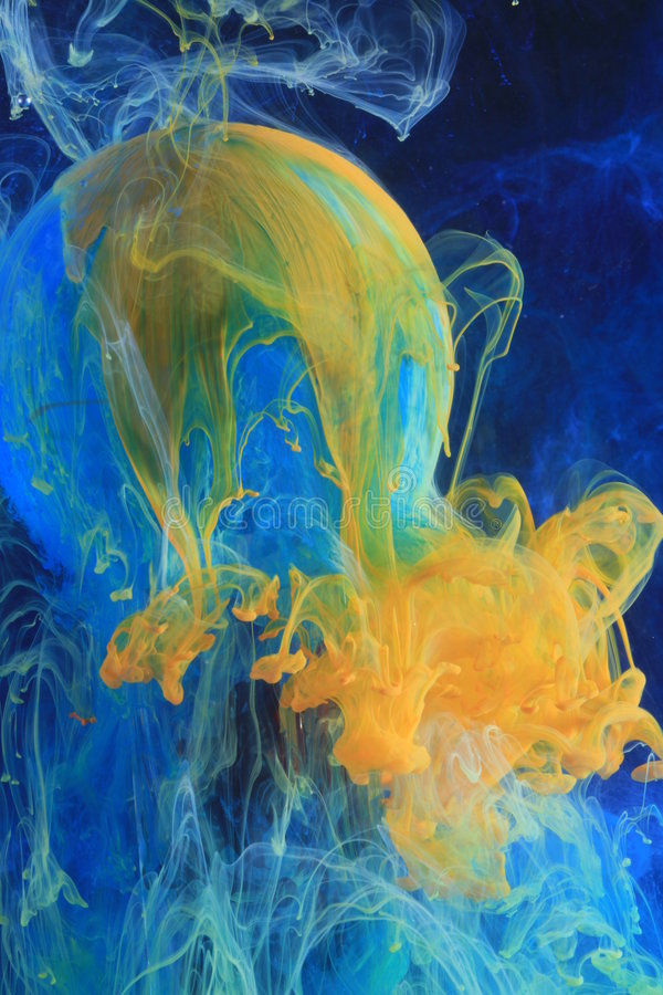 Colors dissolving in water. Blue and yellow colors dissolving in water over a globe of glass, representation tension and turmoil royalty free stock photos