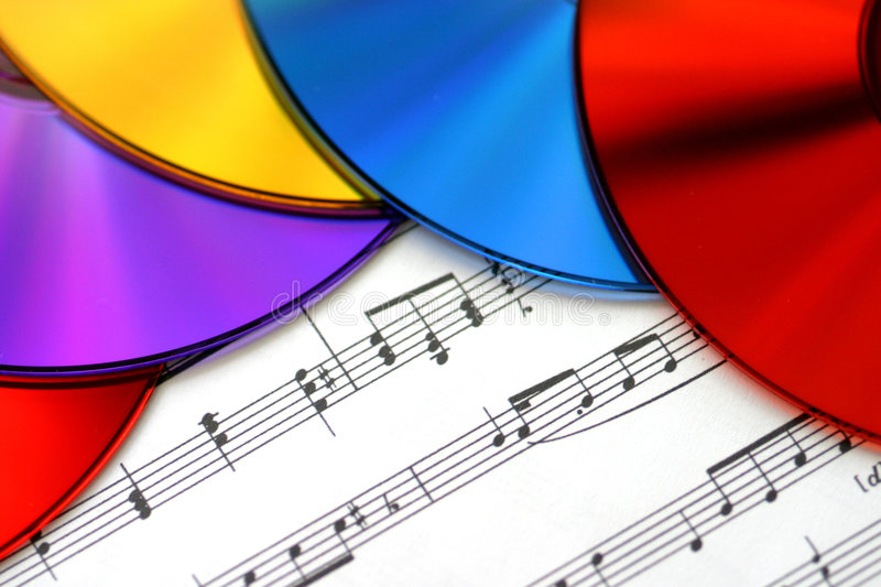 The Colors of Music. Macro shot of colorful CD's on a sheet of music. Can be used to illustrate CD burning, listening to or copying music onto CDs, making music